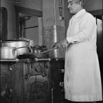Unknown staff member in Norway House School kitchen. Photographs showing interiors and the domestic arrangements are rare for this period. (UCCArchivesWpg bruce45)